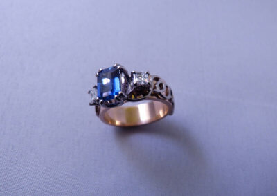 Emerald-cut sapphire and diamond set in palladium and-18ct red ring
