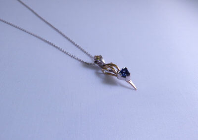 trillion cut tanzanite set in 9ct yellow and palladium pendant